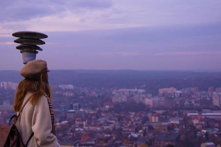 Una niña solitaria con una mochila de cuero con gorra está parada en una montaña alta y observa la ciudad.