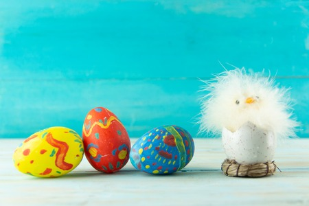 Conceptual image of Easter with baby chicken next to eggs on blue wooden background with copyspace Standard-Bild - 120142635