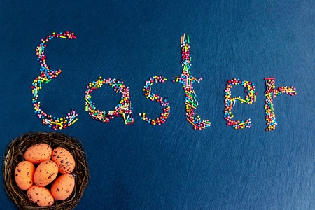 Multicolored candies are laid out in the form of a slice of Easter on a dark blue background Easter concept with Easter eggs in nest