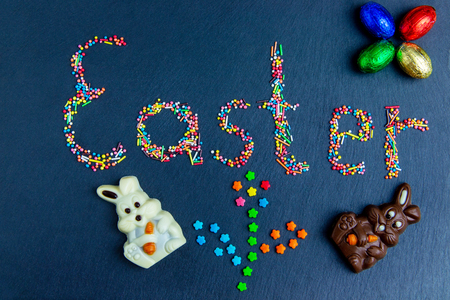 Multicolored candies are laid out in the form of Easter and flower on a dark blue background Easter concept with chocolate Easter eggs and Easter egg in nest.