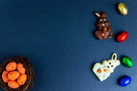 Easter eggs in the nest, chocolate bunny and eggs. Top view on stone table with space for your greetings Stock Photo