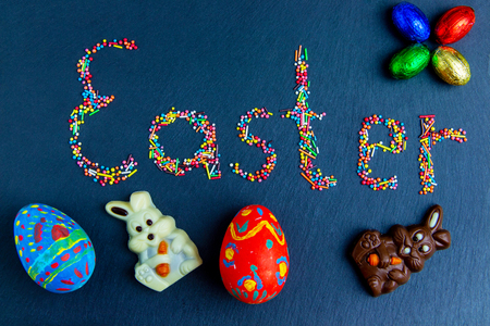 Multicolored candies are laid out in the form of Easter on a dark blue background Easter concept with chocolate Easter eggs and Easter egg in nest.