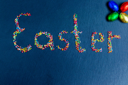 Multicolored candies are laid out in the form of Easter on a dark blue background Easter concept with chocolate Easter eggs
