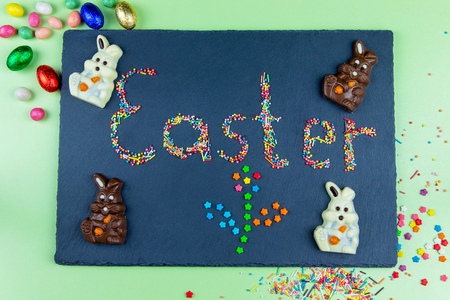 Multicolored candies are laid out in the form of Easter and flower on a dark blue background Easter concept with chocolate Easter bunny