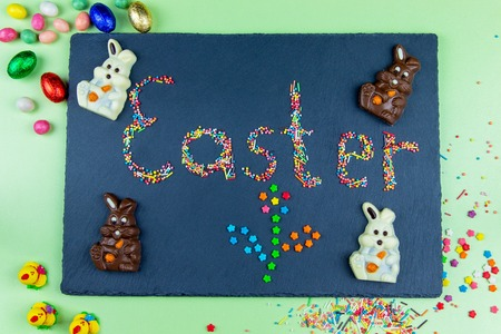 Multicolored candies are laid out in the form of Easter and flower on a dark blue background Easter concept with chocolate Easter bunny and eggs