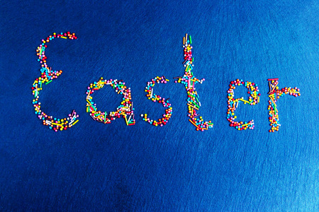 Multicolored candies are laid out in the form of a slice of Easter on a dark blue background Easter concept