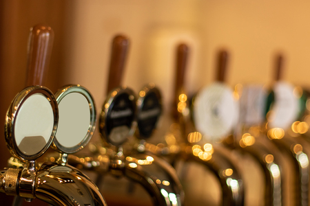 The beer taps in a pub with different kinde of craft beer