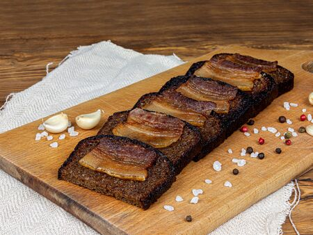 Slices of bacon and parsley on black toasted bread, pork bacon with spices and garlic are on a dark stand. Delicious appetizing sandwich with meat delicacy closeup.