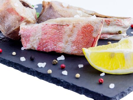 Steak of red grouper fillets with spices, lemon, basil on a dark boards background isolated on white background