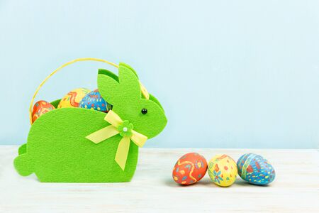 Colorful easter eggs in a bunny basket on a blue background. Easter holidays concept. Copyspace, place for text Banque d'images