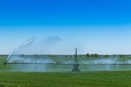 Center pivot crop irrigation or irrigating system for farm management sprays water on the field Stockfoto