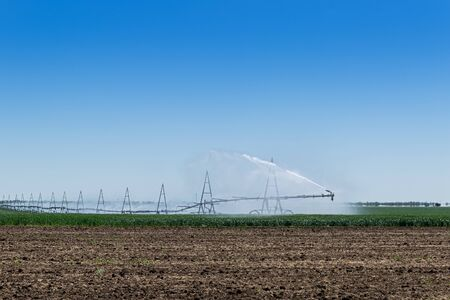 Center pivot crop irrigation or irrigating system for farm management sprays water on the field