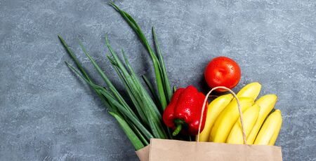 Different food in paper bag on wooden background, close up. Grocery shopping concept, top view 免版税图像
