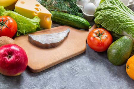 Conceptual image of healthy food balance with fish steak, vegetables and fruits. Nutrition and diet picture with copyspace