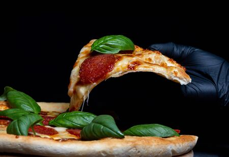Fast food poster, chief cook takes a slice of salami pizza with spinach leaves, hands in rubber gloves close-up side view 免版税图像