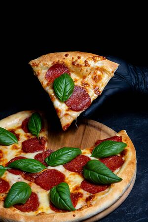 Fast food poster, cook takes a slice of salami pizza with spinach leaves, hands in rubber gloves close-up side view 免版税图像