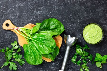 Cooking vegetarian spinach pancakes. Ingredients on the table dill, blender, spinach leaves on wooden board. 免版税图像