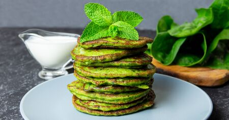 Delicious healthy breakfast with spinach pancakes and yogurt sauce on blak background 免版税图像