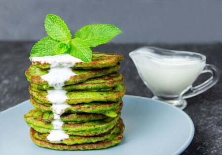 Green pancakes with spinach on black background next to sour cream 免版税图像
