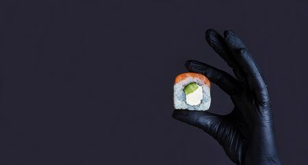 Diet food concept. Female hand in rubber gloves holding sushi salmon roll on a dark background with copyspace. Sushi menu. Japanese food.