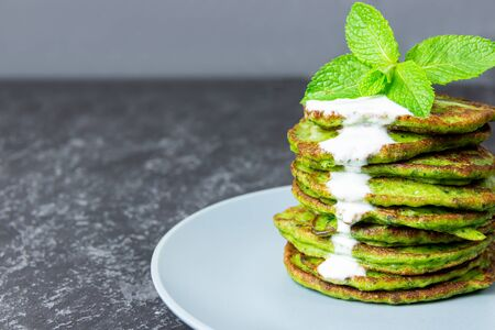 Green spinach pancakes with mint and yogurt on black background next to sour cream