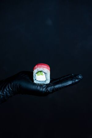 Female hand in rubber gloves holding sushi tuna roll on a dark background 免版税图像