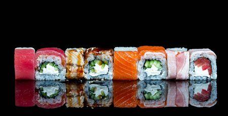 Sushi rolls set isolated Philadelphia roll, california with fresh ingredients on black background. Sushi menu. Japanese food.