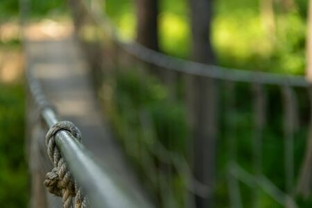 Detail of the suspension bridge laying and in the background the unfocused bridge and the thick vegetation of the monteverde forest. 免版税图像 - 150454671
