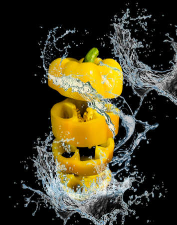 Nutrition and diet food picture with sliced fresh sweet pepper on black background.