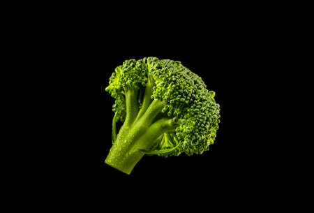 Nutrition and diet food picture with fresh green broccoli with water drops on black background