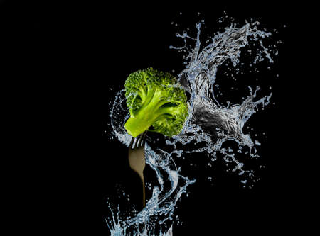 Nutrition and diet food picture with fresh broccoli on fork and water splash isolated on black background