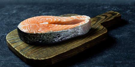 Fresh raw salmon fish steak on dark stone background. Creative layout made of fish Healthy food concept