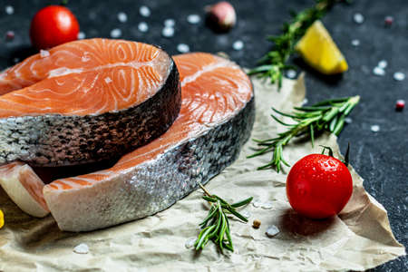Two fresh raw salmon steaks with salt, peppers, lemon, tomatoes and rosemary on the rustic paper Creative layout made of fish, top view, flat lay, mockup, overhead. Healthy food concept