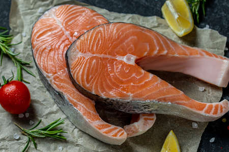 Healthy food concept Raw trout fish steaks, pepper and salt, herbs on rustik paper background, top view