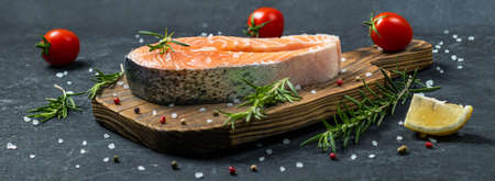 salmon steak with vegetables and spices on a wooden background. The concept of cooking. Grocery background. healthy eating vegetables and salmon
