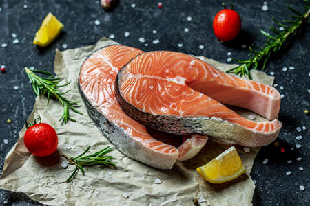 Healthy eating vegetables and salmon Raw trout fish steaks, pepper and salt, herbs on rustik paper background, top view 免版税图像