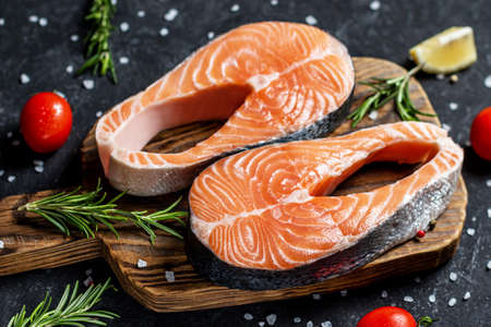Healthy food concept Raw trout fish steaks, pepper and salt, herbs on black wooden table, top view