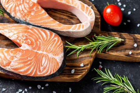 Healthy food concept Red Fish Steak with spices on dark wooden background.