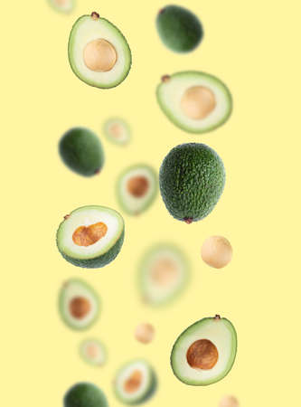 Creative layout with ripe flying avocado halves on yellow background. Healthy food, diet, tropical exotic fruit, trendy food product. Minimalistic summer food concept. Organic avocado. Pop art design 免版税图像