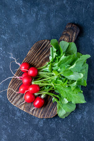 Bundle of fresh garden radish with leafs from organic farm on dark background. Top view with copy space
