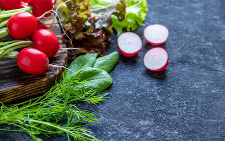 Frash organic vegetables from farmer market on rustic wooden board. Picture with radish, salad, spinach and dill. 免版税图像