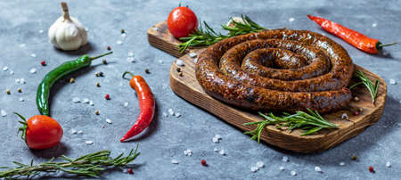 Spiral homemade sausage ring baked in an old oven is on a wooden board with pepper and garlic 免版税图像