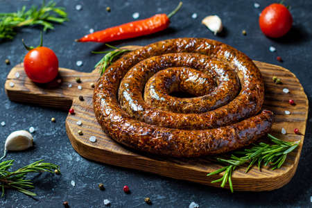 Spiral sausage top on a serving Board with tomatoes, rosemary, pepper, salt, garlic and spices 免版税图像
