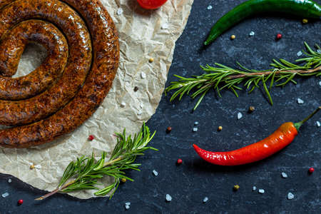BBQ spiral sausage from pork and beef meat on parchment. Dark background. Top view. Sausage bbq grill with tomatoes, rosemary, peppers, salt, garlic, spices and vegetables.