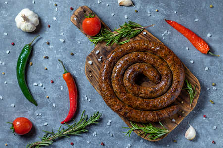 Smoked round ring beef sausages on wooden board with tomatoes, rosemary, pepper, salt, garlic, spices