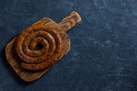 BBQ spiral sausage from pork and beef meat on a wooden cutting board. Dark wooden background. Top view