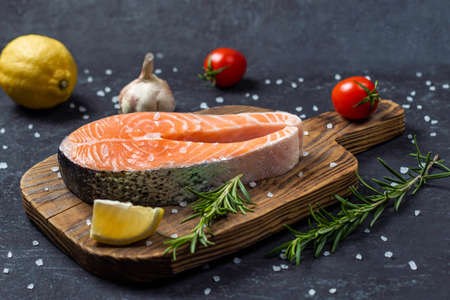 Healthy food concept, raw salmon with spices and vegetables on the graphite board.