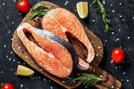 Two fresh raw salmon steaks with salt, peppers, lemon, tomatoes and rosemary on the rustic table Creative layout made of fish, top view, flat lay, mockup, overhead. Healthy food concept
