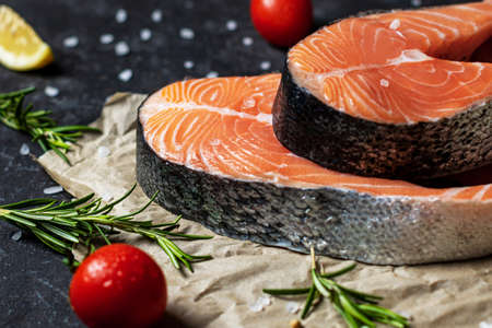 Healthy food concept with raw salmon fillet, salt, peppers, lemon, tomatoes and dill on the rustic paper 免版税图像