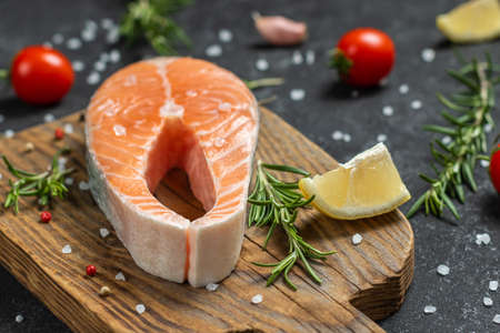 Fresh raw salmon fish steak with spices on dark wooden background. Creative layout made of fish, top view, flat lay, mockup, overhead. Healthy food concept 免版税图像